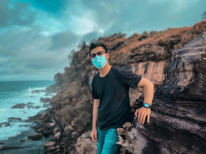 Young man wearing mask standing on rock by sea against sky