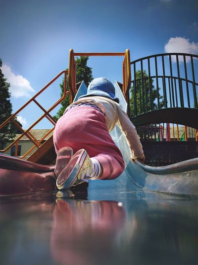 Rear view full length of child on slide at playground