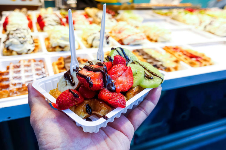 Cropped hand of person holding waffle and fruits in container at shop