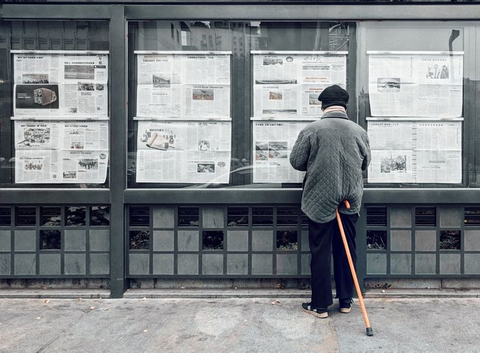 Rear view of mature man reading newspaper while standing on street