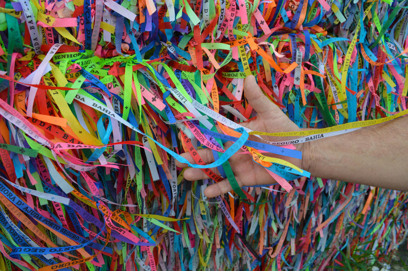 Close-up of hand touching multi colored ribbons