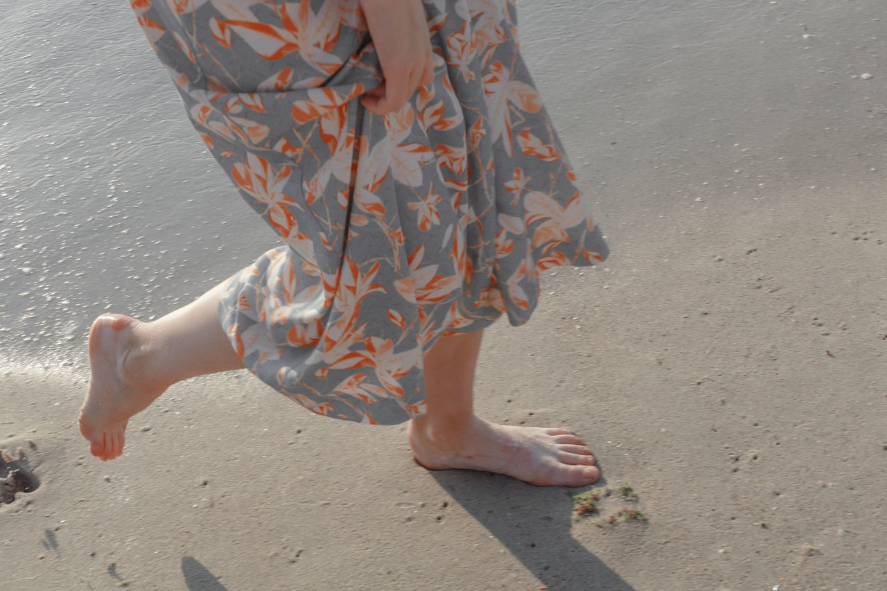 Low section of woman walking at beach