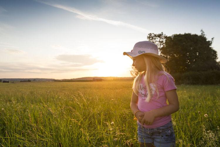 Full length of girl on field against sky during sunset