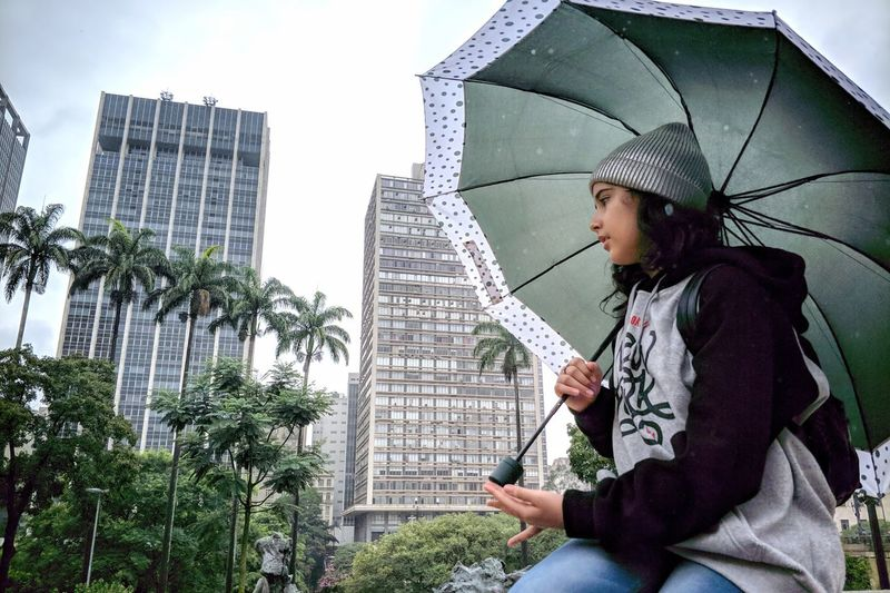 Low angle view of girl holding umbrella against building