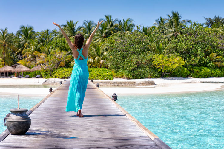 Happy traveler woman in a blue summer dress walks towards a tropical island in the Maldives Water Lifestyles Rear View Leisure Activity Women Day Sky Sea Turquoise Colored Beauty In Nature Arms Raised Outdoors Dress Woman Happy Travel Concept Island Tropical Climate Pier Beach Walking Vacations Holiday Maldives