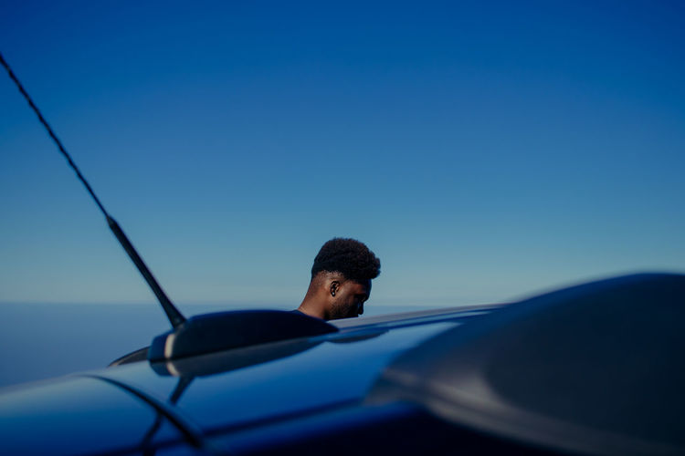 Man by car against blue sky