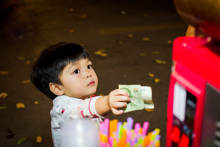 High Angle View Of Boy Holding Paper Currency