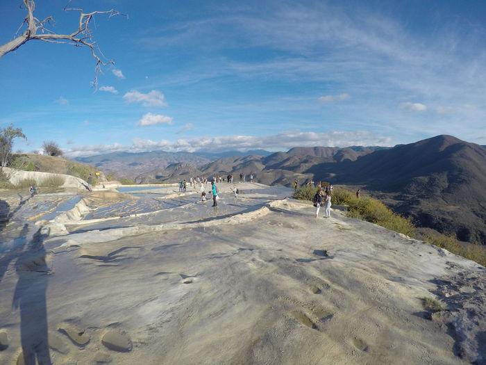 People on salt pan on mountain against sky