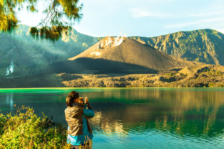 Rear view of woman photographing lake against mountains and sky