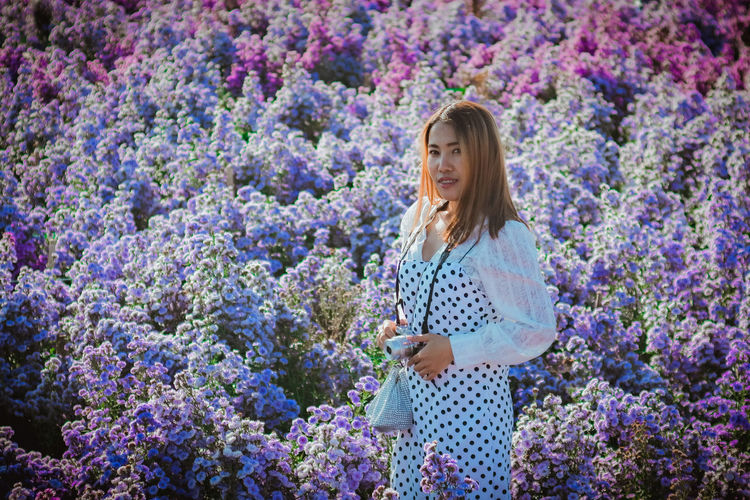 Woman standing in front of flowering plants
