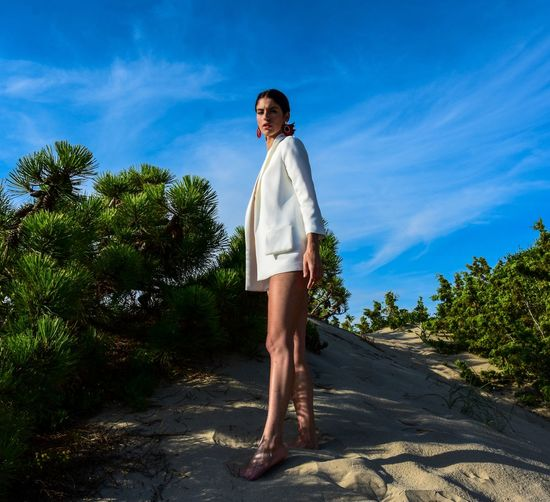 Side view portrait of young woman wearing white blazer standing on sand against sky