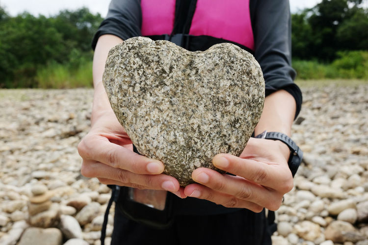 Midsection of woman holding heart shape rock at beach