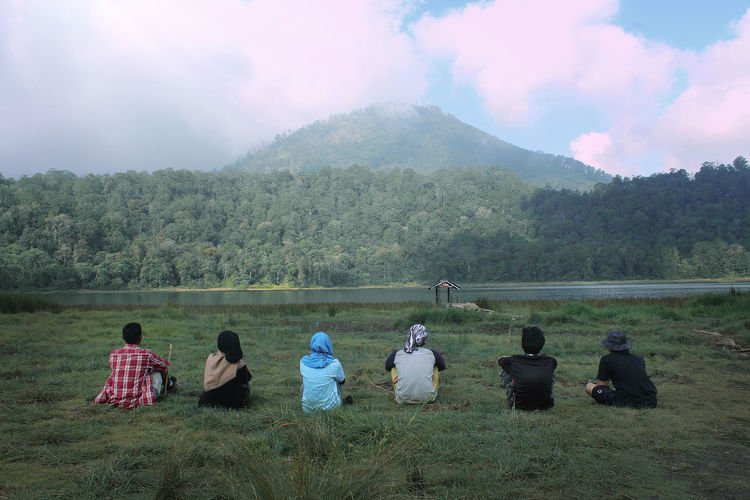 Rear view of people sitting on field by mountain against sky