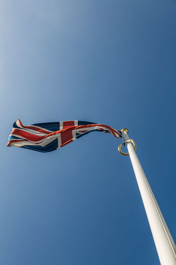 Low angle view of british flag against clear blue sky