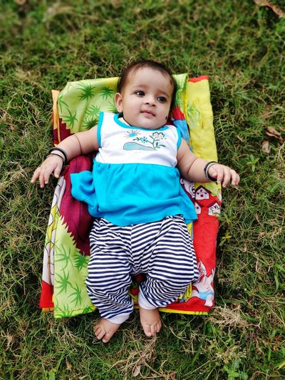 Cute Baby Girl Lying On Sheet Over Field At Park