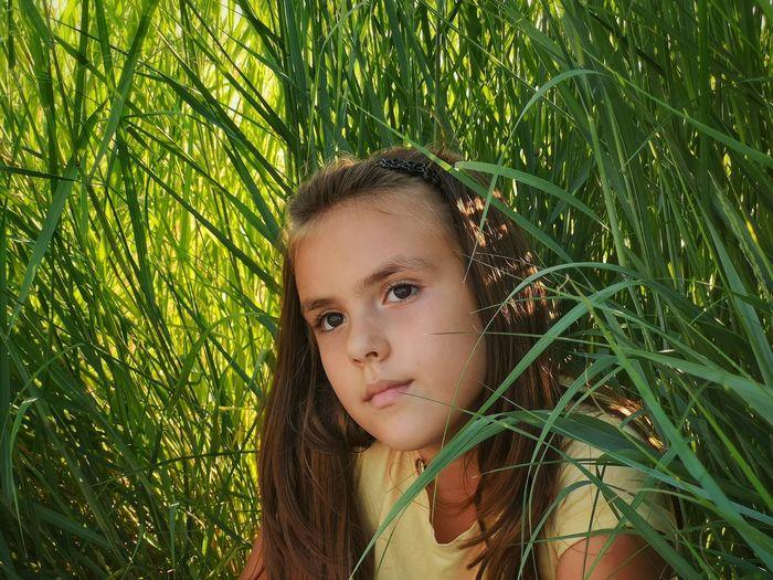 Portrait of teenage girl on plant in field