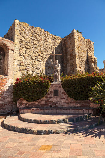 San Juan Capistrano, CA, USA —September 25, 2016: Statue of Fray Junipero Serra at the Mission San Juan Capistrano in Southern California, United States. Editorial use only. Architecture Church Day Flowers Fray Junipero Serra Garden Landmark Landscape Mission Mission San Juan Capistrano No People Outdoors Ruins San Juan Capistrano San Juan Capistrano Mission Statue United States United States Landmark
