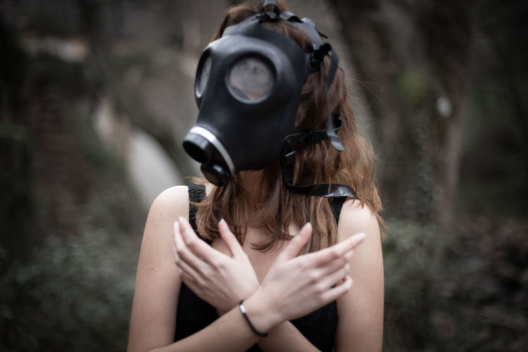 Woman wearing gas mask while covering chest