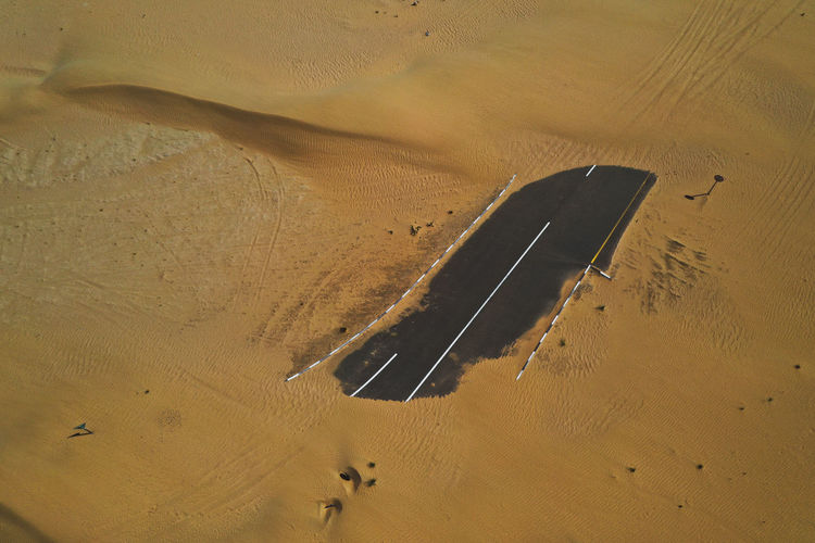 Drone shot of an asphalt road covered in sand in the desert.