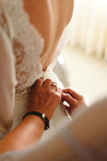 Midsection of woman assisting bride during wedding