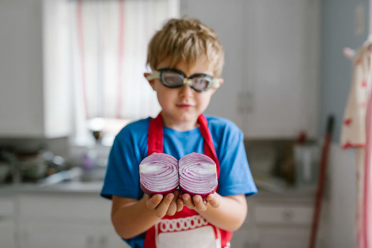 Boy holding halved onion in kitchen at home