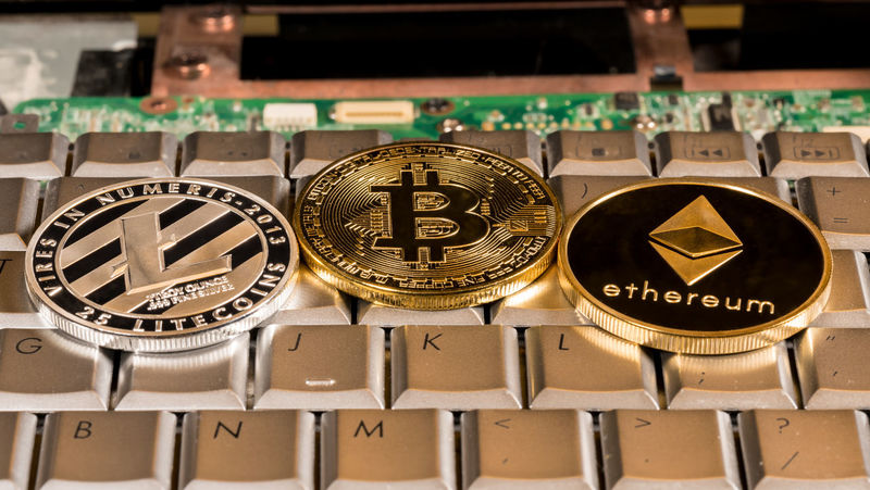 Ethereum, bitcoin and litecoin coins on computer keyboard to illustrate the rise of new cyber currencies Currency Trading Bitcoin Blockchain Coin Coins Computer Cybercurrency Ethereum Finance Financial Litecoin Technology