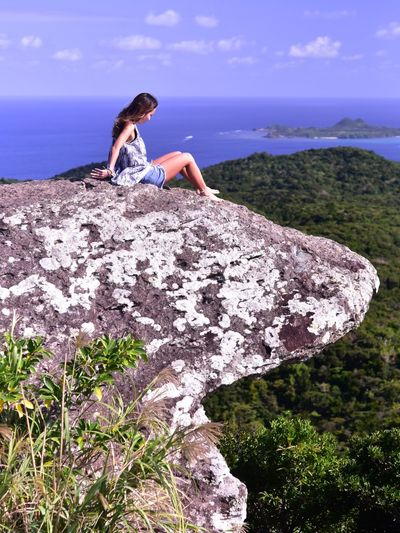 Woman sitting on rock by sea against sky