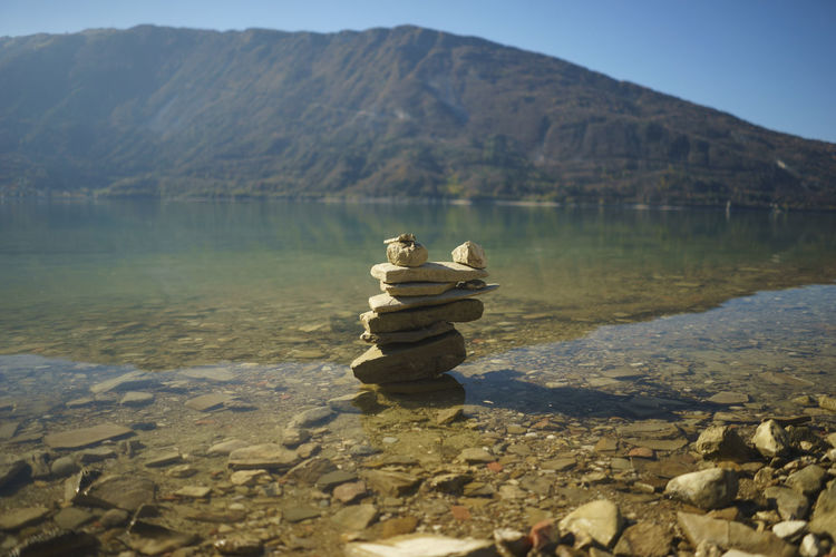 Stack of rocks at lakeshore against mountain