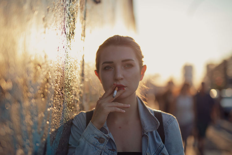Young woman smoking while standing by wall in city