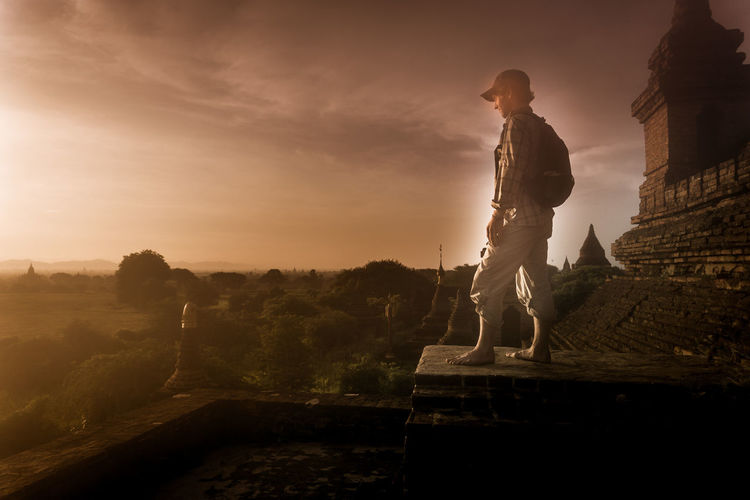 Side view of man standing on old ruin at sunset