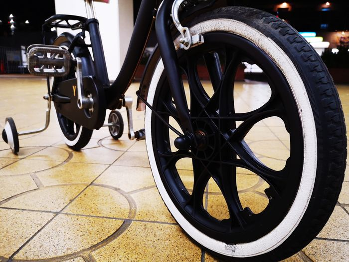 Close-up of bicycle parked on tiled floor