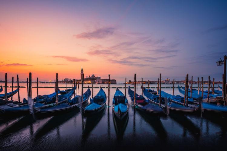 Gondolas moored at harbor during sunset
