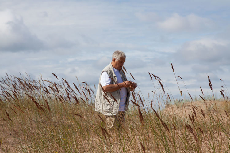 Mature man standing on field against sky