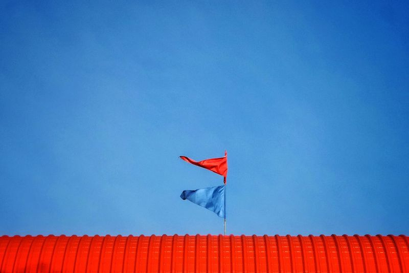 Low angle view of flags on red roof against blue sky