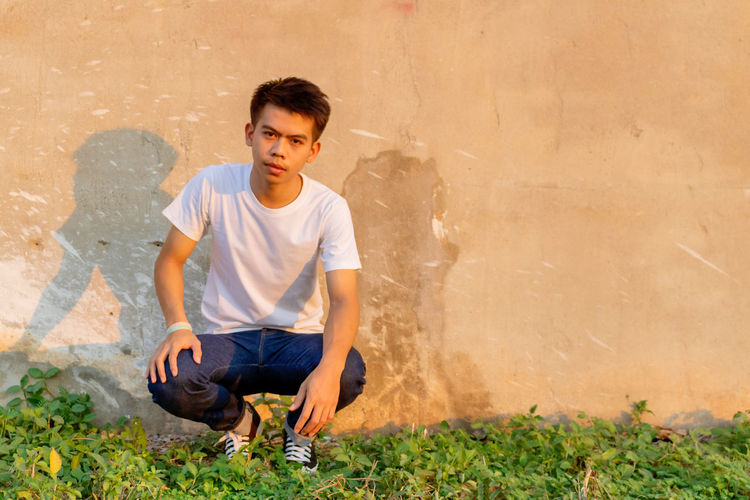 Full length of young man sitting against wall