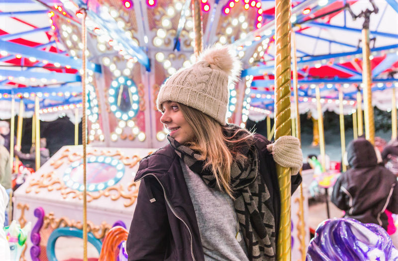 Thoughtful young woman sitting on illuminated carousel at night