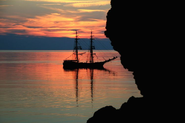 Silhouette tall ship sailing in sea at sunset
