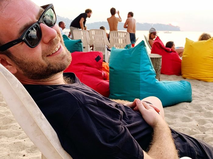 Smiling man wearing sunglasses while resting at beach