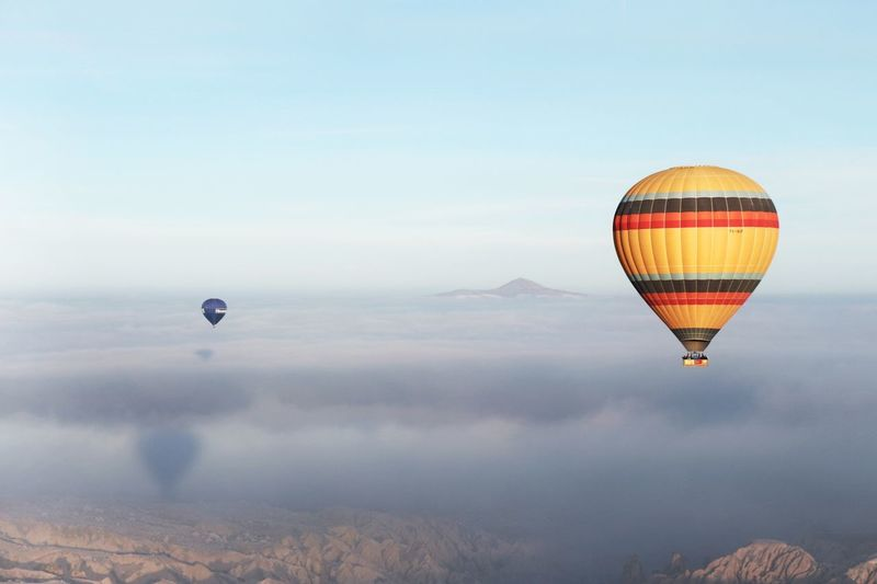 Two hot air balloons rising up and escaping the low clouds in Cappadocia Turkey EyeEmNewHere EyeEm Best Shots Amazing Experience Wanderlust Travel Experience Cloudy Clouds Low Clouds Colorful Hot Air Balloons Hot Air Balloon Hot Air Ballooning Türkiye Turkey Kappadokya Cappadocia Hot Air Balloon Mid-air Flying Adventure Sky Beauty In Nature Mountain Nature Air Vehicle Outdoors Cloud - Sky Scenics No People Go Higher