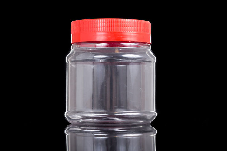 Plastic jar bottle container with red cover lid against dark background Black Background Bottle Close-up Container Copy Space Cut Out Food And Drink Glass - Material Healthcare And Medicine Indoors  Jar No People Plastic Reflection Single Object Studio Shot Transparent