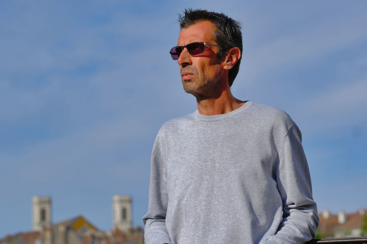 Young man wearing sunglasses standing against sky