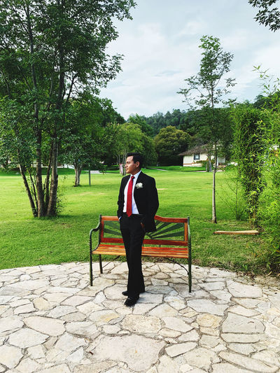 Full length of man wearing suit standing in park