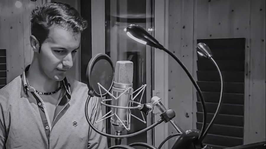 Young Man Standing By Microphone In Recording Studio