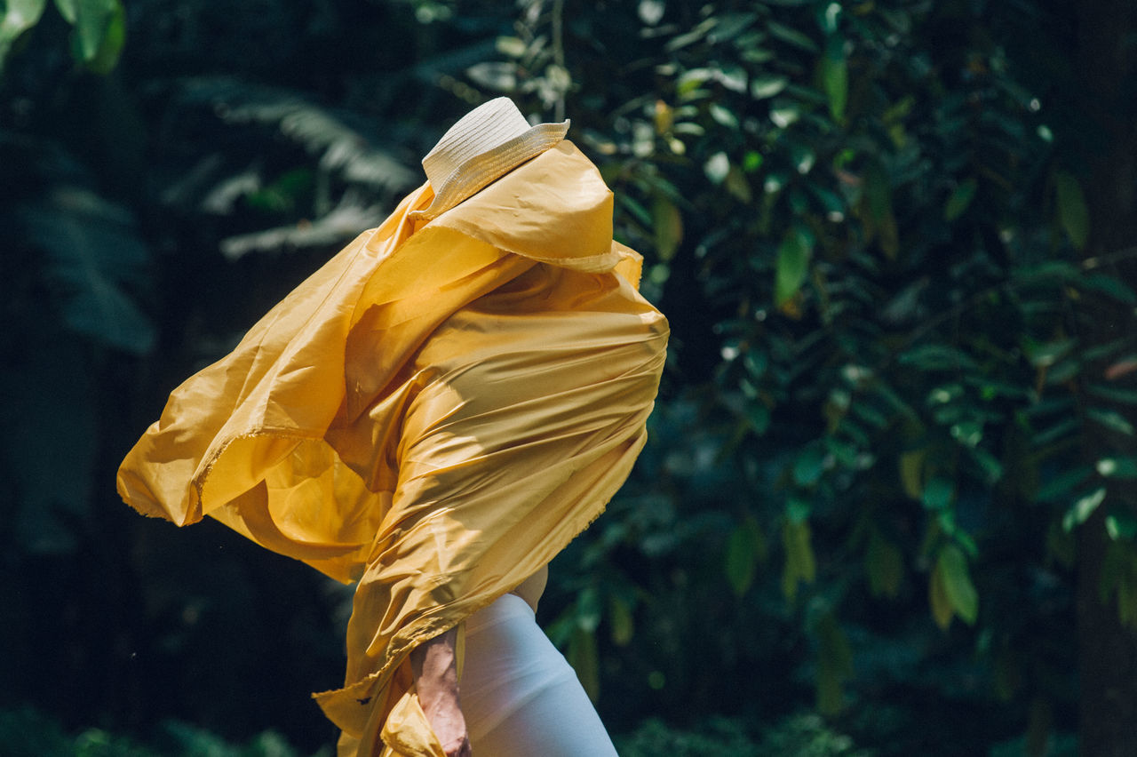 Side View Of Man Covering Face With Yellow Fabric