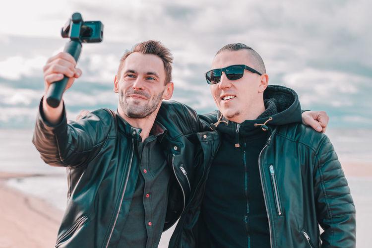Man taking selfie with friend against sky