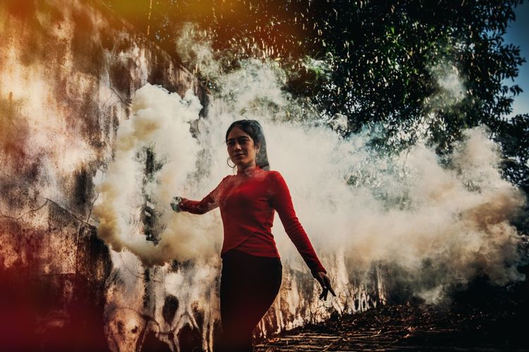 Young woman standing amidst smoke in forest