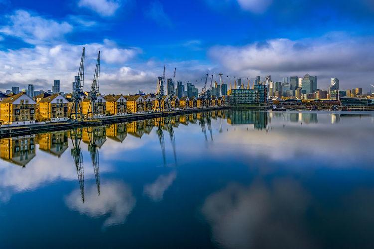 Bridge over river by buildings against sky in city