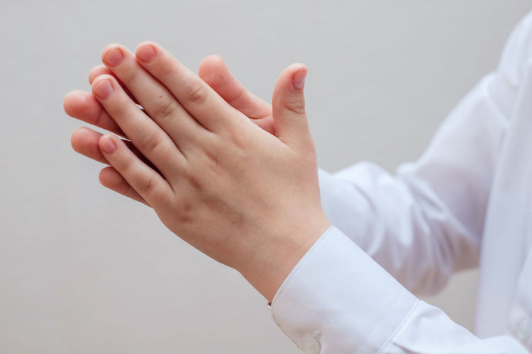 Close-up of hands over white background