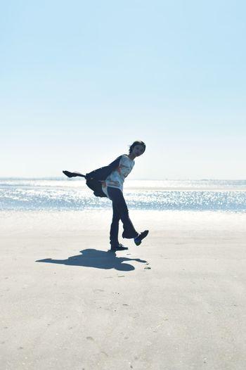 Full length of man surfing on beach against clear sky