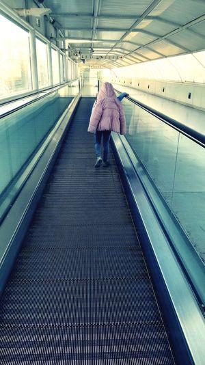 Rear view of woman walking on escalator